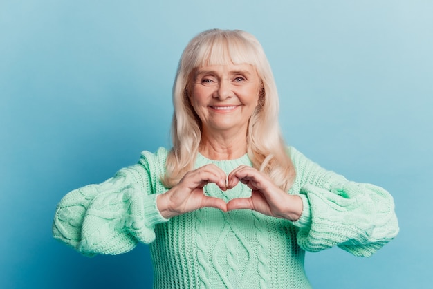 Photo of old woman show heart fingers love symbol isolated over blue background