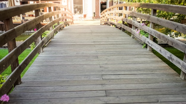 Photo of old wooden bridge with flower pots in old european town
