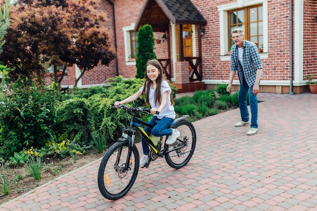 Photo of older, bearded grandfther is learning daughter to ride a bike in the house yard.