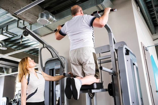 Photo of older couple in the gym. man doing pull-up exercise