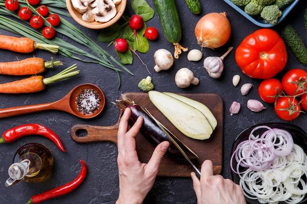 Фото сверху свежие овощи, шампиньоны, разделочная доска, масло, нож, баклажан, руки шеф-повара