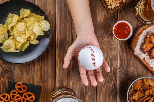 Фото сверху стола с закусками, руки с бейсболом