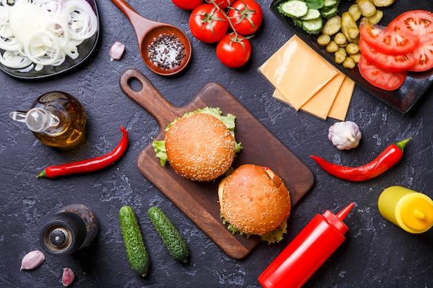 2つのハンバーガー、唐辛子、チーズ、トマトの上の写真