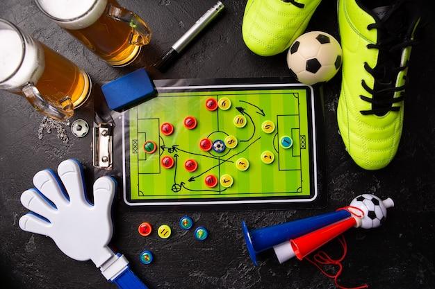 泡ビール、テーブルサッカー、ボール、サッカーブーツ、パイプ、黒いテーブルの上のガラガラのおもちゃの2つのマグカップの上の写真