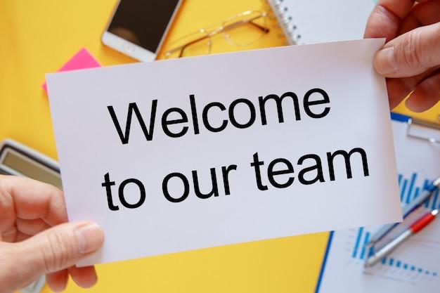 텍스트가있는 작업 공간 카드 위에있는 사진-노란색 배경에 저희 팀에 오신 것을 환영합니다.