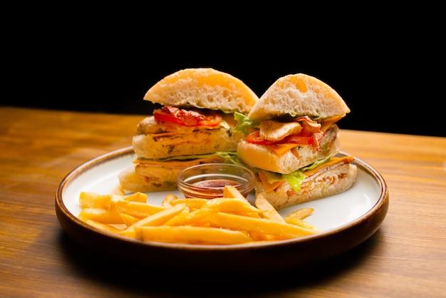 チキンとフライドポテトとケチャップの大きなサンドイッチの木製テーブルの写真