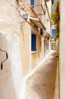 Photo of one of cozy and little streets full plants in sunny and warm greece