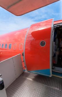 Photo of open door of big civil airplane painted in red