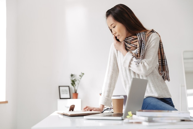 Photo of optimistic asian female worker wearing white sweater reading business diary and smiling while sitting on table in office