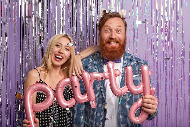 La foto del marito e della moglie ottimisti tiene un palloncino a forma di lettera rosa