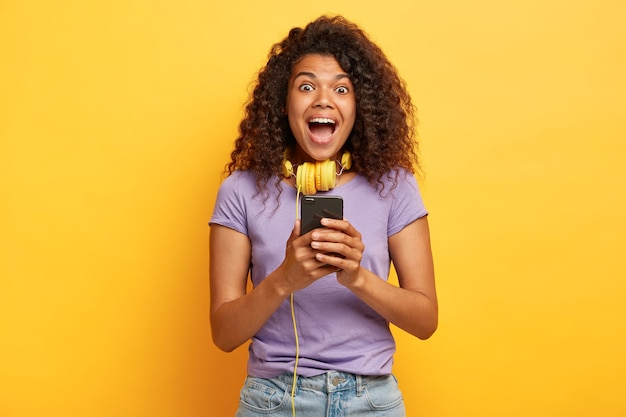 Foto di giovane donna ipermotiva con acconciatura afro in posa contro il muro giallo