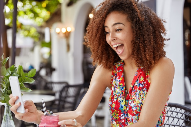 Photo of overjoyed african american female holds modern mobile phone, makes video call, communicates with friends while recreats in cafeteria