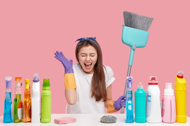 Photo of overjoyed brunette woman keeps hand near face, exclaims and laugh happily, wears headband, rubber gloves