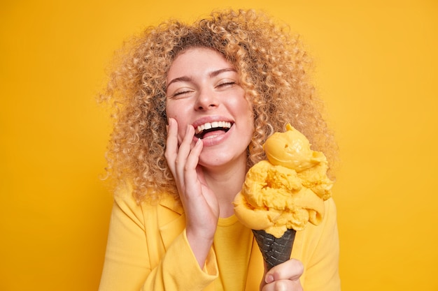 Photo of overjoyed curly haired woman feels amused smiles broadly keeps eyes closed enjoys eating delicious ice cream of mango flavor poses with yummy frozen dessert isolated on yellow wall.