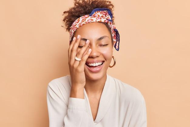 Photo of overjoyed dark skinned female model makes face palm smiles