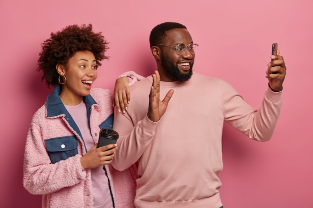 Photo of overjoyed dark skinned woman and man take selfie on modern gadget, wave palm at camera, drink aromatic coffee, stand together against pink space