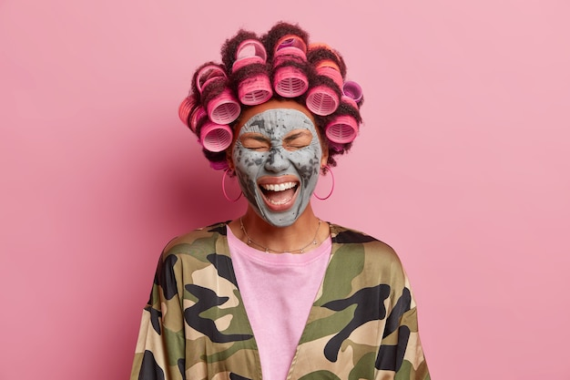 Photo of overjoyed ethnic woman laughs out loudly fels very happy enjoys facial treatments wants to have fabulous look makes hairstyle reduces wrinkles with nourishing clay mask. beauty concept