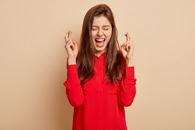 Photo of overjoyed lovely dark haired female crosses fingers for good fortune, sincerely believes in victory, keeps eyes closed, dressed in red blouse, gestures over beige  wall. body language