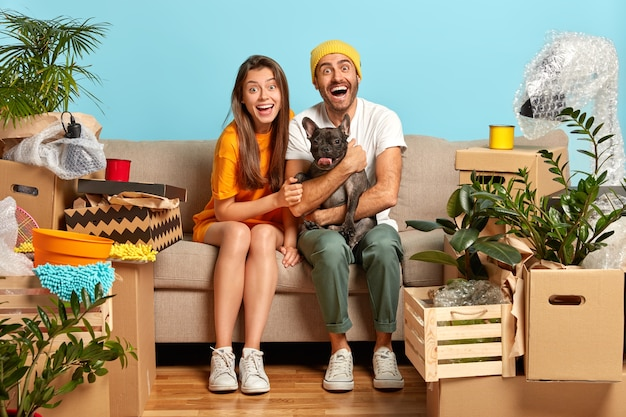 Photo of overjoyed married family couple rest on sofa during moving day, play with black pedigree bulldog, many packages with household items around. two renters in abode
