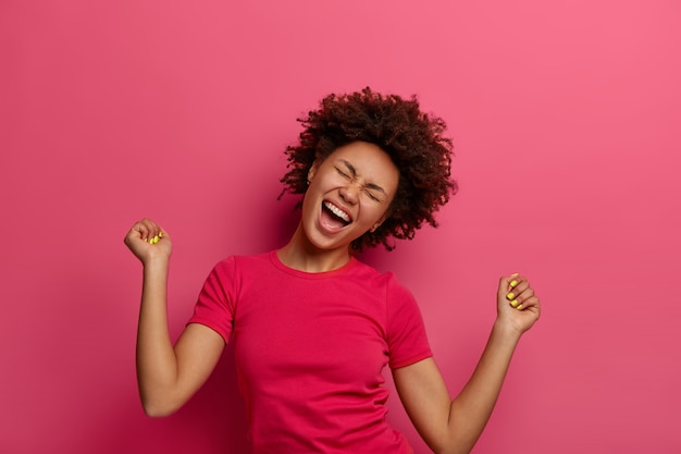 Photo of overjoyed woman triumphant makes fist bump, tilts head and laughs with joy, celebrates own success, wears casual t-shirt, gets victory and achieves goal, poses over pink wall.