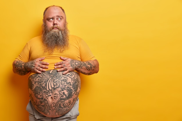 Photo of overweight pensive man keeps hands on big belly with tattoo, thinks and looks aside, has thick beard, poses against yellow wall. obese guy unable to realize how tummy could appear