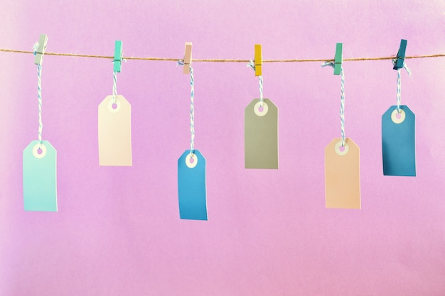 A photo on a pale lilac background. on the rope, with crumpled colored clothespins