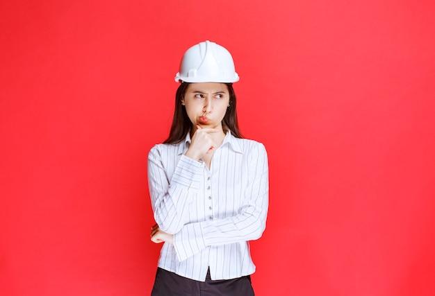 Foto di una donna d'affari pensierosa che indossa un cappello di sicurezza in piedi contro il muro rosso.