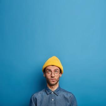 La foto di un uomo pensieroso e concentrato guarda pensieroso sopra, indossa un cappello giallo, camicia di jeans, grandi occhiali rotondi, si trova sopra il muro blu, copia l'area dello spazio verso l'alto
