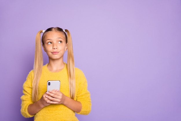 Photo of pensive contemplating looking girl staring into empty space to find idea with telephone in hands isolated in yellow sweater over pastel violet color wall