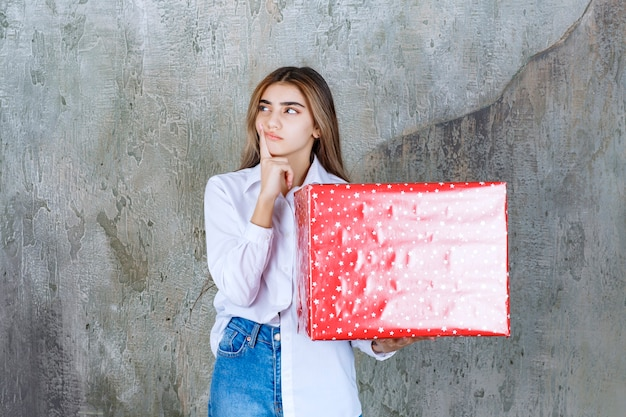 Foto di una modella pensierosa con i capelli lunghi che tiene in mano un grande regalo rosso