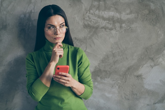 Photo of pensive thoughtful bewildered puzzled woman touching chin looking into empty space in spectacles holding telephone isolated grey color wall concrete background