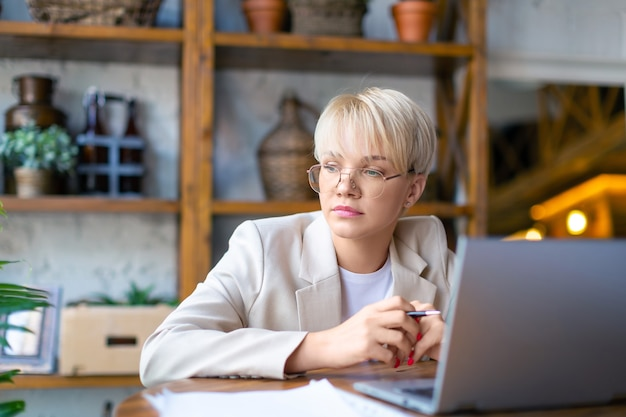 Photo of a pensive woman in front of a laptop monitor she works with documents and papers at home  c...