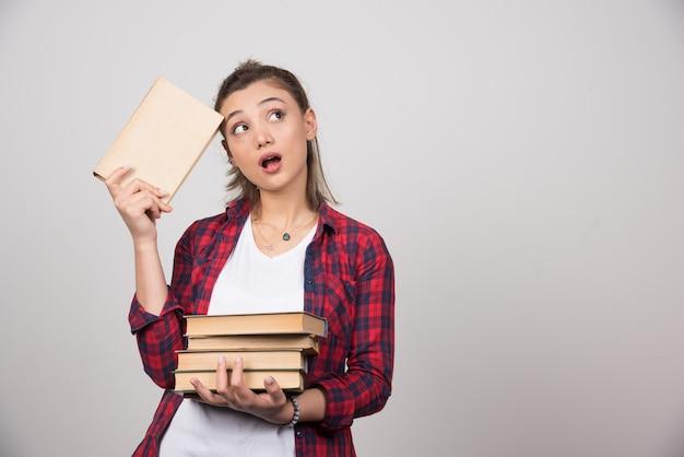 Foto di un giovane studente pensieroso in possesso di una pila di libri.