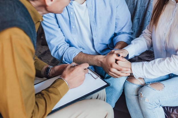 Photo of people hands holding on meeting with psychologist at home