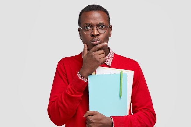 Photo of perplexed indignant black man holds chin, carries folders and papers, stares  with stupefied expressions
