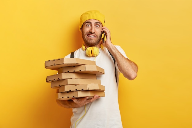 Photo of pizza man receives orders from customers via smart phone, holds many carton boxes with fast food, has unpleasant look to speak with dissatisfied client. service and delivering concept