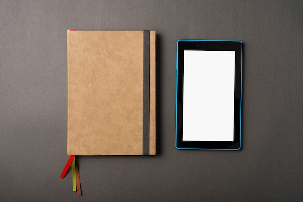 A photo of a planner and a tablet near it on a dark table