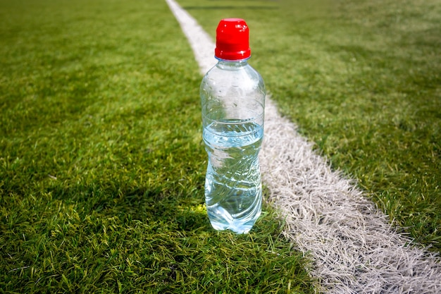 Photo of plastic bottle of water on green grass at football field