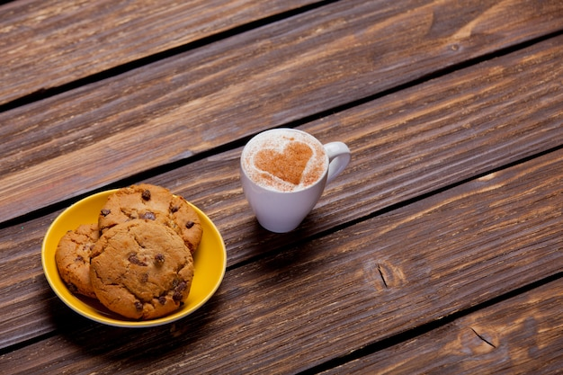 Photo of plate full of cookies and cup of coffee on the wonderful brown wooden background
