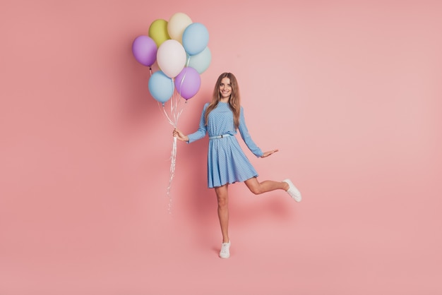 Photo of playful girl with colorful air balloons in short skirt shoes on pink background