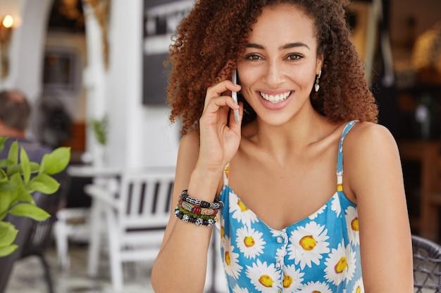 Foto di una donna afroamericana dall'aspetto piacevole con un'espressione allegra, chiama un amico tramite cellulare, gode del tempo libero durante il giorno d'estate