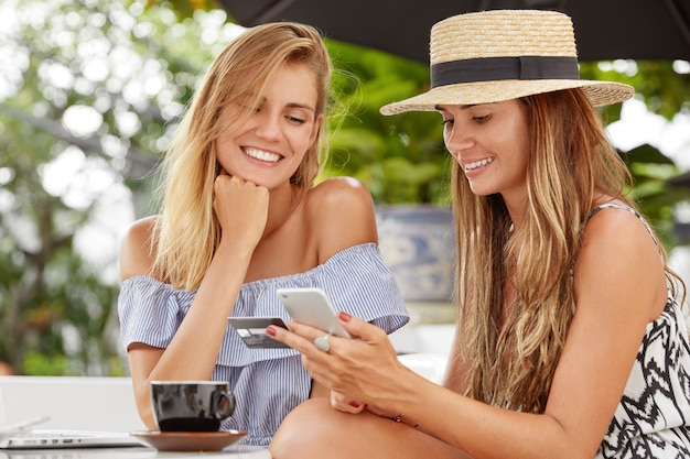 Photo of pleasant looking two women have rest in coffee shop, choose new purchase. attractive young female dials number of credit card on mobile phone, pays online. people and spare time concept