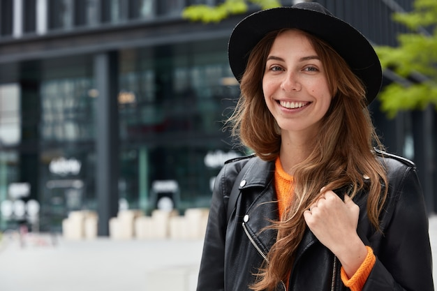 Foto di giovane turista femminile dall'aspetto piacevole posa con un sorriso felice in strada