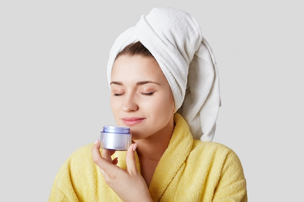 Photo of pleased adorable young woman holds bottle of cream and smells it, going to make mask on face after taking bath, isolated over white wall. people, cosmetics and beauty concept.