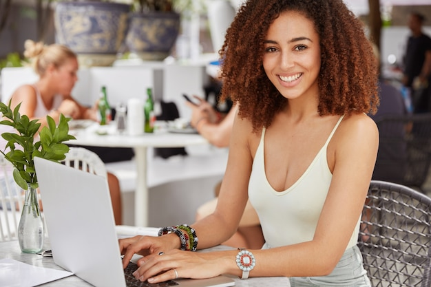 Foto della femmina afroamericana soddisfatta con un ampio sorriso brillante, vestita casualmente, tastiere sul computer portatile