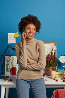 Photo of pleased afro american freelancer stands in own cabinet at home, has phone conversation, looks aside with broad smile, poses near desktop with desk lamp