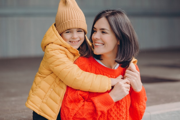 Photo of pleased attractive young mother looks positively at daughter