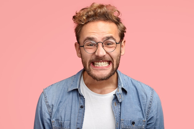 La foto dell'uomo caucasico riccio soddisfatto sorride allegramente