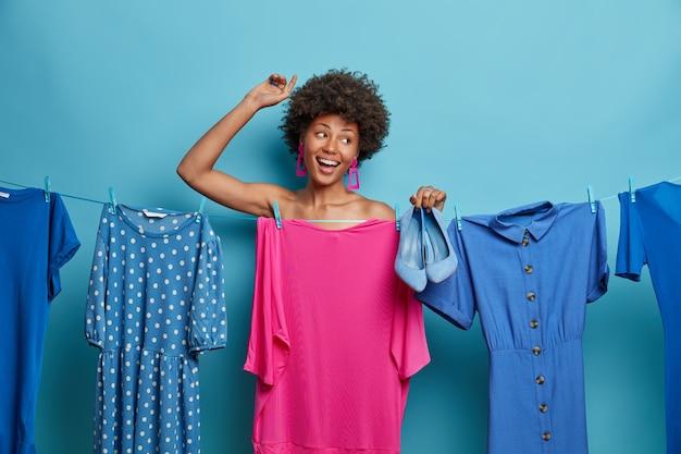 La foto della donna dai capelli ricci felice balla con la mano alzata, sceglie i vestiti per le vacanze, la festa corporativa o il compleanno, va al concerto, posa nuda dietro l'abito appeso, tiene le scarpe blu