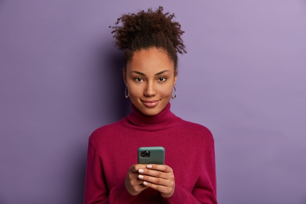 Photo of pleased dark skinned millennial girl holds mobile phone, waits for call, texts with friend in online chat, uses special application, taps smartphone screen, checks newsfeed, browses internet